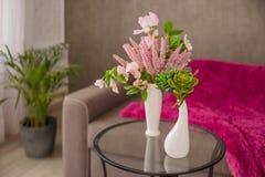 Salon int?rieur ? la maison confortable avec un sofa brun et un vase avec des fleurs et articles de d?cor sur une petite table co image stock