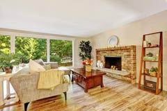 Salon lumineux spacieux avec le mur de verre et la cheminée de brique image stock