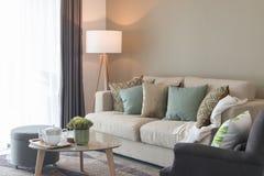 salon moderne avec les oreillers verts sur le sofa confortable et la La en bois Photographie stock libre de droits