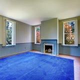 Salon non meublé avec la cheminée antique et le tapis bleu photo libre de droits