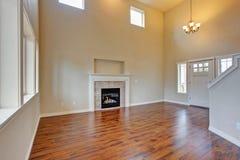 Salon spacieux, cheminée et nouveau plancher en bois dur images stock