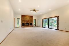 Salon vide très grand avec la cheminée de brique. photographie stock libre de droits