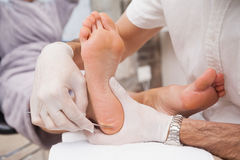 Salon worker using a scalpel. To clean customers foot Stock Image
