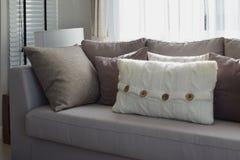 Salone con la fila dei cuscini grigi sul sofà Fotografia Stock