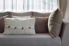 Salone con la fila dei cuscini grigi sul sofà a casa Immagine Stock