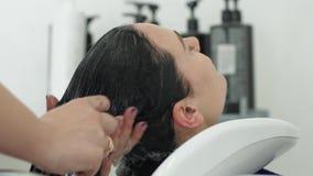 Salone del parrucchiere, lavante testa della ragazza in lavandino sotto la doccia al salone di bellezza archivi video