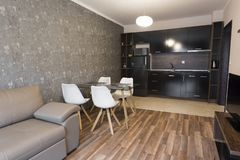 Salone dello spazio aperto con la cucina Nuova casa Stanza con la mobilia marrone di tono di colore Fotografia interna Pavimento  fotografia stock