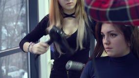 Salone di bellezza barbershop Lo stilista asciuga i capelli del suo cliente L'allievo aiuta lo stilista che lo stilista conduce l stock footage