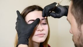 Salone di bellezza Estetista maschio in guanti neri che applicano l'eye-liner del sopracciglio prima della procedura permanente d archivi video