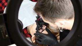 Salone di bellezza Estetista maschio in guanti neri che fanno procedura permanente di trucco sul ringiovanimento femminile del Fa archivi video
