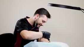Salone di bellezza Estetista maschio in guanti neri che fanno procedura permanente di trucco sul ringiovanimento femminile del Fa stock footage
