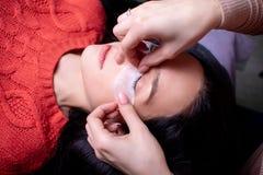 Salone di bellezza, fine di procedura di estensione del ciglio su Bella donna con capelli lunghi immagine stock