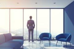Salone grigio, sofà blu, sottotetto, uomo d'affari Immagine Stock