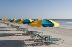 Salones y paraguas en Daytona Beach imagenes de archivo