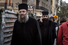 SALONIKI GRECJA, GRUDZIEŃ, - 24, 2015: Dwa grka Orrthodox księdza chodzi w ulicach Thessaloniki, jeden ma telefon c zdjęcia stock