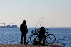 SALONIKI GRECJA, GRUDZIEŃ, - 25, 2015: Sylwetka starzy rybacy na Saloniki nadbrzeżu, morze egejskie obraz stock