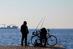 SALONIKI, GRIECHENLAND - 25. DEZEMBER 2015: Schattenbild von alten Fischern auf Saloniki-Seeseite, Ägäisches Meer Stockbild