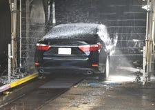 Saloon car going through car wash Royalty Free Stock Photos