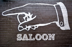 Saloon sign and symbol. Wall painting mural on a brick wall of a hand point at the direction way to a Saloon. sign and symbol Stock Photo