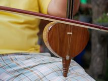 Salor, two or three-string spike fiddle used in the Lanna region or in the North of Thailand, being played. Salor being played, two or three-string spike fiddle stock photography