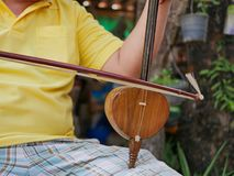 Salor, two or three-string spike fiddle used in the Lanna region or in the North of Thailand, being played. Salor being played, two or three-string spike fiddle royalty free stock images