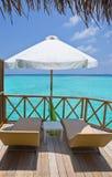 Salotti del chaise e del parasole su un terrazzo di acqua v Immagine Stock Libera da Diritti