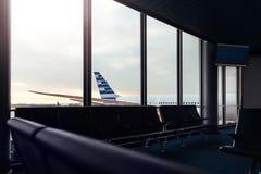 Salotto dell'aeroporto con la vista del fondo dell'aeroplano attraverso la finestra fotografie stock libere da diritti