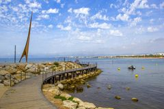 Salou, Tarragona, Spain - June 09, 2017: Wooden walkway to the Mediterranean Sea at the monument on the Costa Dorada. Public domai royalty free stock photos