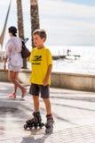 SALOU TARRAGONA, SPANIEN - SEPTEMBER 17, 2017: En pojke åker rullskridskor på vid havet Kopiera utrymme för text vertikalt Royaltyfri Bild
