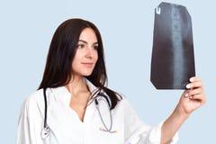 Salowego shotof lekarki lub pielęgniarki przyjemni przyglądający żeńscy spojrzenia przy X promieniem attentively i szczęśliwie, s obrazy stock