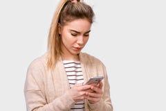 Salowy portret sfrustowany młodej kobiety gospodyni domowej mienia telefon komórkowy w ona ręki czyta wiadomości od ona famliy fotografia royalty free