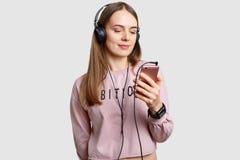 Salowy strzał skupiający się w ekranie mądrze telefon nastoletnia dziewczyna, słucha muzykę z hełmofonami od playlisty, cieszy si obraz royalty free