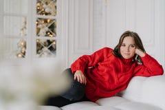 Salowy strzał ładna ciemna z włosami kobieta w ciepłej zimie odziewa, opiera, gotowego, kłama na wygodnej białej kanapie, patrzej zdjęcia royalty free