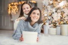Salowy strzał matka i córka zabawę, części teraźniejszość wpólnie, być w pokoju dekorującym z girlandami i choinką, brzęczenia zdjęcia stock