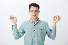 Salowy strzał podnosi ręki w zen gescie i gapi się przy kamerą zdecydowany skupiający się atrakcyjny mężczyzna w koszula, Obraz Stock