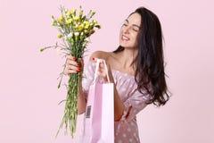 Salowy strzał przyjemni przyglądający młoda kobieta uśmiechy delikatnie, ubierająca modna suknia, trzyma prezent torbę i pięknych obraz stock