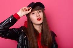 Salowy strzał szczęśliwa Kaukaska młoda nastolatek dziewczyna w czerwonym hoodie, skórzana kurtka, stojaki z zuchwałym wyrazem tw zdjęcia royalty free