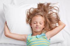 Salowy strzał uroczy mały żeński dzieciak z uncombed lekkim włosy, utrzymuje ręki pod miękką poduszką, ubierającą w pyjamass, poz zdjęcie stock
