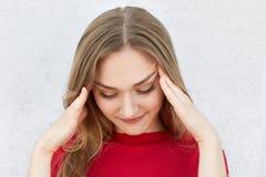 Salowy strzał zmęczona jasnogłowa kobieta trzyma jej ręki na świątyniach ma migrenę po ciężkiej pracy patrzeje w dół w czerwonym  obraz royalty free