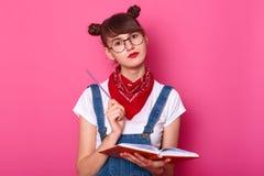 Salowy studio strzał zadumany rozważny młody uczeń z czerwoną pomadką na jej twarzy, trzymający notatnika i pióro w jej rękach, zdjęcia stock