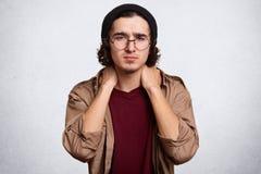 Salowy studio strzelał przystojny poważny młody faceta pozować odizolowywam nad białym tłem w studiu, dotyka jego szyję z oba zdjęcia royalty free