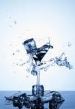Salpica del agua Cubos de hielo que caen en una copa de agua imagen de archivo