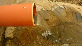 Salpicar el agua del tubo plástico del dren está corriendo abajo al canto rodado y a las burbujas almacen de video