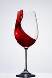 Salpicar el vino rojo en la copa elegante que se opone a fondo ligero con la reflexión Fotografía de archivo