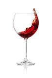 Salpicar el vino rojo en un vidrio Imágenes de archivo libres de regalías