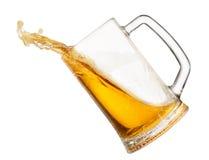 Salpicar la cerveza en taza fotos de archivo
