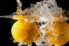 Salpicar la naranja en el agua Fotografía de archivo libre de regalías