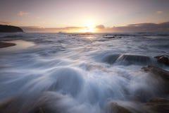 Salpicar la onda con salida del sol Imagen de archivo