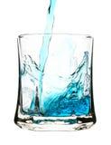 Salpique, bebida azul se está vertiendo en el vidrio Fotografía de archivo