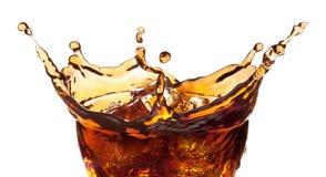 Salpique de los cubos de hielo en un vidrio de cola Imagen de archivo libre de regalías